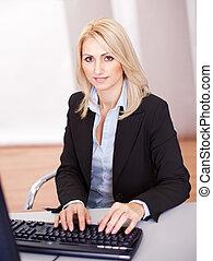 Beautiful businesswoman working on computer