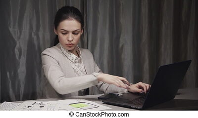 Beautiful businesswoman working with laptop and documents while sitting at table in home.