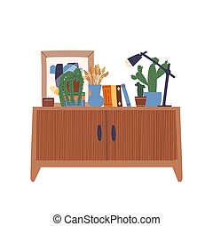 Beautiful cabinet with various books, a vase with dried grass bunches, a lamp, plants, poster in a frame, an candle.