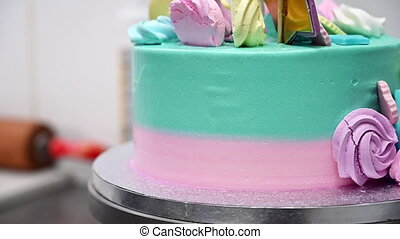 Beautiful cake decorated with sweet products rotates around ...