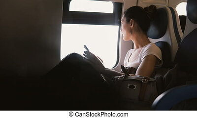 Beautiful calm Caucasian female commuter checking smartphone app traveling in a train car, looking at the window.
