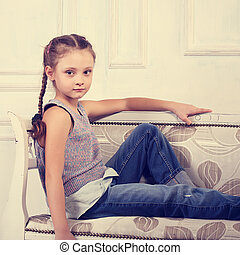 8924b6c3b Beautiful calm happy kid girl sitting on the bench in blue jeans and fashion  blouse looking