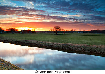 beautiful calm  sunset over river in farmland