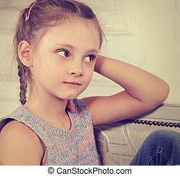 4a14d9435 Beautiful calm thinking kid girl sitting on the bench in blue jeans and fashion  blouse looking