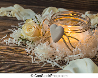Beautiful candle and rose on wooden bacground. Close up