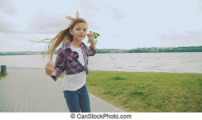 Beautiful carefree young girl walking on the lawn. Slow motion