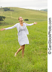 carefree young woman arms open in grassland