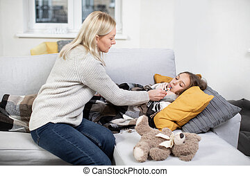 Beautiful caring confident 40-aged woman mother, using thermometer, measuring temperature of her sick teen daughter, lying on soft couch in living-room, covered with blanket