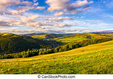 beautiful Carpathian countryside at sunset. village down in...