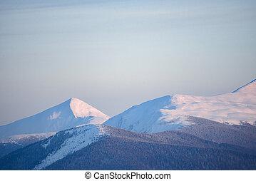 Beautiful Carpathian Mountains in Fog. Winter Sunset Landscape.