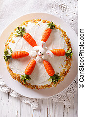 Beautiful carrot cake with candy bunny close-up. vertical top view