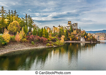 Beautiful castle by the lake at dusk in autumn