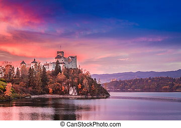 Beautiful castle by the lake in autumn at dusk