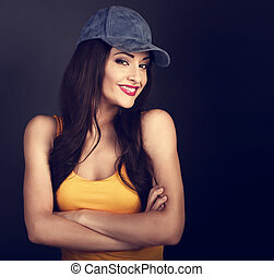 Beautiful casual smiling woman in blue baseball cap and yellow top looking with folded arms on grey background with empty copy space. Closeup portrait