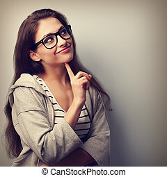Beautiful casual thinking young woman in glasses looking up. Vintage portrait