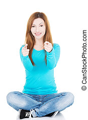 Beautiful casual woman sitting pointing on camera.