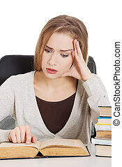 Beautiful casual woman student worried, scared is sitting by a desk and stack of books. Isolated on white.