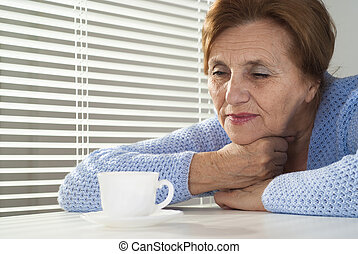 Beautiful caucasian aged woman with a cup