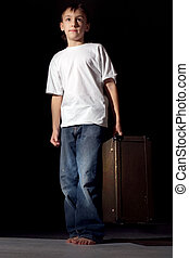 Beautiful Caucasian boy standing with a suitcase