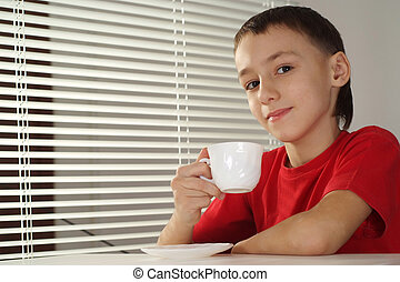 Beautiful caucasian boy with a cup of tea