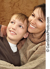 Beautiful Caucasian boy with his mother sitting
