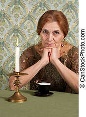 Beautiful Caucasian elderly woman sitting at a table
