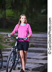 Beautiful Caucasian Female Biker with Mountain Bike Walking On Starirs Outdoors.