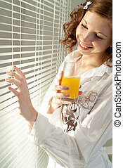 Beautiful Caucasian female standing with juice
