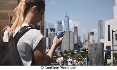 Beautiful Caucasian girl confused looking at smartphone near amazing Manhattan financial center panorama, New York City.