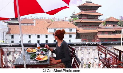 Beautiful Caucasian girl eating breakfast, lunch at rooftop, Kathmandu, Nepal,