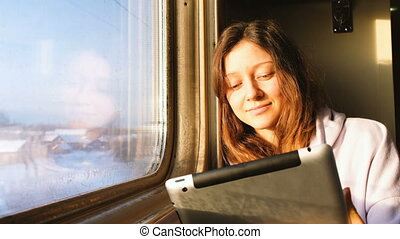 Beautiful caucasian girl enjoys a tablet on the train, smiling and looks out the window at sunset, 4k.