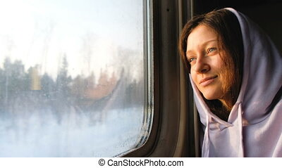 Beautiful caucasian girl looking out the window at sunset on a train, 4k.