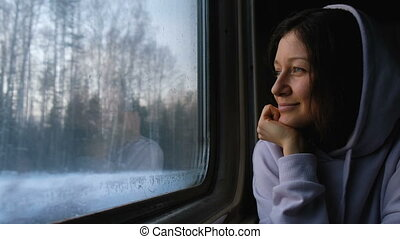 Beautiful caucasian girl looks at nature through the train window, 4k.