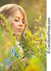 Beautiful caucasian girl smelling flowers