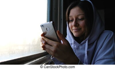 Beautiful caucasian girl uses a phone in a train on the Trans-Siberian highway, 4k.