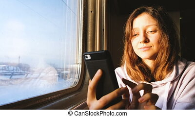 Beautiful caucasian girl uses the phone on the train and...