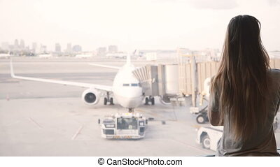 Beautiful Caucasian girl with long hair walks up to airport...