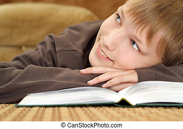 Beautiful Caucasian lad sitting on the couch with a book