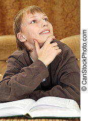 Beautiful Caucasian man sitting on the couch with a book