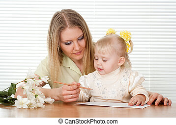 Beautiful Caucasian mother and daughter sitting at a table
