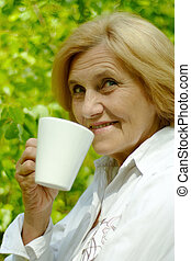 Beautiful Caucasian old woman with a cup