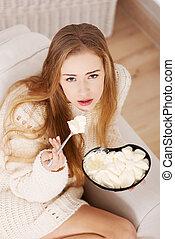 Beautiful caucasian sad woman eating ice creams.