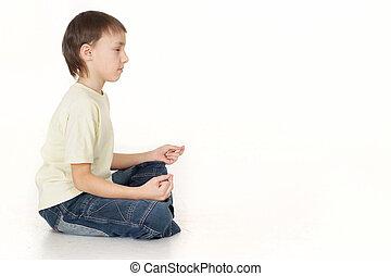 Beautiful Caucasian teenager sitting sideways and meditates
