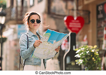 tourist woman looking at the map on the street