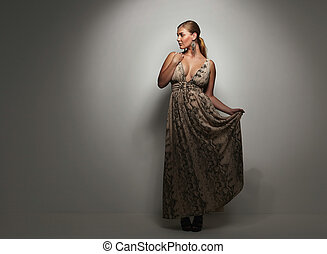 Beautiful caucasian woman in an elegant cocktail dress poses in the studio. Oversized female model on grey background.