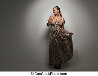 Beautiful caucasian woman in an elegant cocktail dress poses...