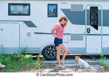 Beautiful caucasian woman is training a dog next to the motorhome. Travel with your pet in a mobile RV. Red-haired girl playing with Jack Russell Terrier. Female trailer driver.