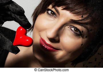 Beautiful caucasian woman with little red heart in hand
