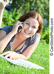 Beautiful Caucasian young woman portrait speaking on phone with book on green grass
