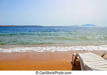 Beautiful chaise longue on the shore of the warm sea during tide. Egypt, Sharm El Sheikh.
